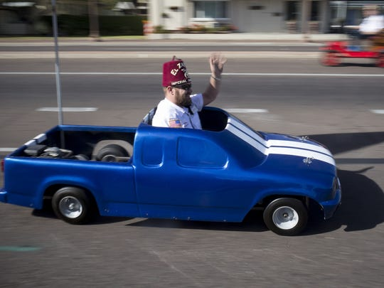A Shriner waves from his vehicle during Tempe's Veterans Day Parade on Nov. 10, 2017.