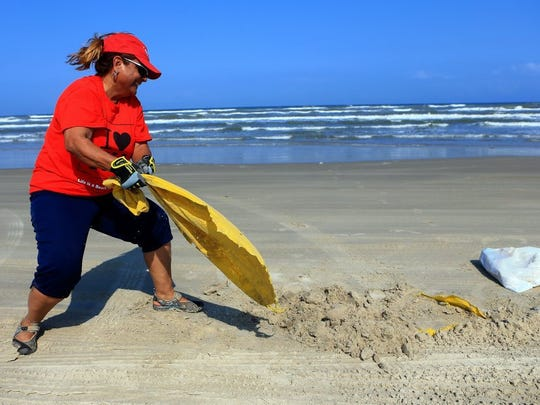 GABE HERNANDEZ/CALLER-TIMES Realtor DeeDee Cortez pulls a plastic bag caught in the sand during the Keller Williams Red Day Beach Cleanup on Thursday, May 12, 2016, at Padre Island National Seashore in Corpus Christi.
