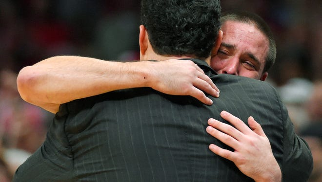Arizona guard T.J. McConnell hugs coach Sean Miller as he leaves the game against Wisconsin on Saturday.