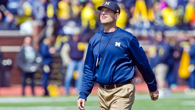 Michigan head coach Jim Harbaugh walks the field between downs during the NCAA college football team's spring game in Ann Arbor, Mich. Now Harbaugh will finally begin coaching the Wolverines in some actual games _ but no matter how this first season in Ann Arbor goes, the quirky, khaki-wearing coach has unified a fractured Michigan fan base.