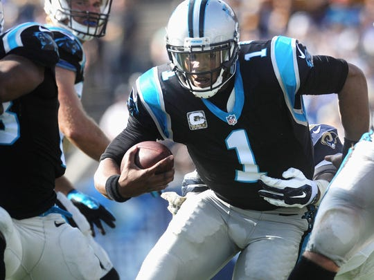 Panthers quarterback Cam Newton escapes a sack and carries the ball against the Rams defense at the Colisuem Sunday. Carolina won the game 13-10.