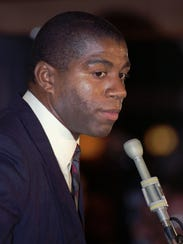 Magic Johnson pauses during a news conference on Nov.