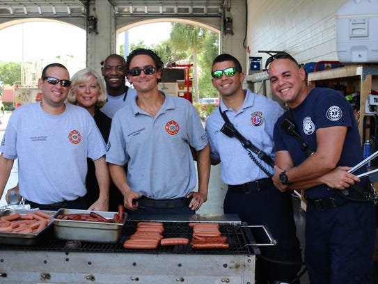 EMTs and firefighters cooking up hotdogs for the guests.
