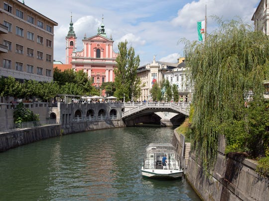 In this Friday, Aug. 12, 2016 photo, tourists and residents walk across Tromostovje bridges in downtown Ljubljana, Slovenia. The tiny European nation of Slovenia is undergoing a tourism boom partly because it is the native country of U.S. first lady Melania Trump.