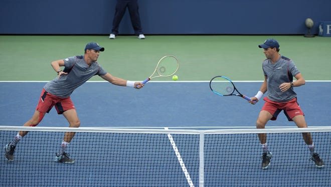 Bob Bryan, left, hits a return at the net while brother Mike Bryan during this year's U.S. Open. The Camarillo twins have reached the semifinals in their quest for their 17th Grand Slam title and first since 2014.