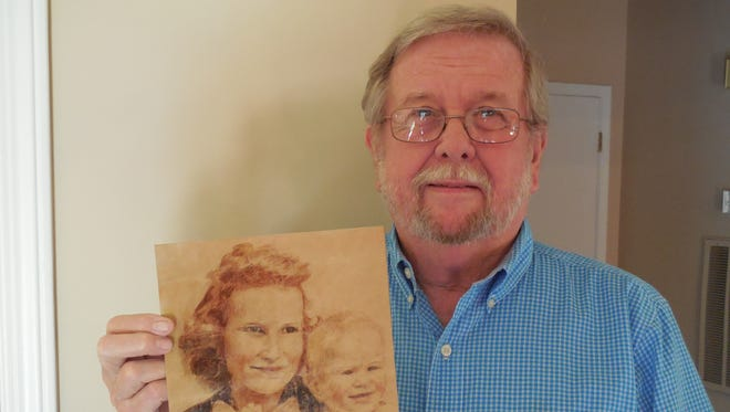 Jim Akin holds a sketch of his mother, Annie, and himself that was drawn in 1945 during World War II. A German prisoner of war at a Paris hospital used a wallet-sized portrait carried by Jim's father, Dick Akin, as the model for his pencil sketch.