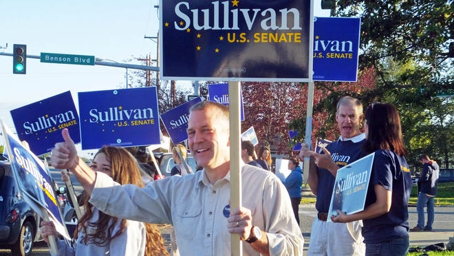 Dan Sullivan, candidate for the Republican candidate for election to the U.S. Senate, waves along a busy street on the morning of Alaska's primary election Tuesday, in Anchorage.