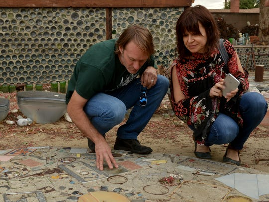 """Traveling from Baltimore just to see Grandma Prisbrey's Bottle Village, Kurt Deemer and his wife, Kasia, look closely at the details created by Tressa """"Grandma"""" Prisbrey in Simi Valley."""