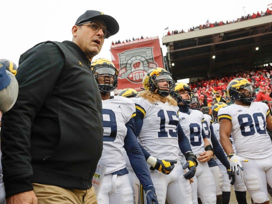 Jim Harbaugh leads his team on to the field vs. Wisconsin last season.