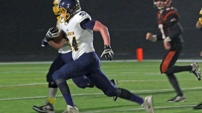 In addition to playing tight end and linebacker on the Quabbin Regional football team, Jake Warburton, shown running with the ball against Gardner High last Thanksgiving Eve, also played a season of baseball for the Panthers during his junior year.