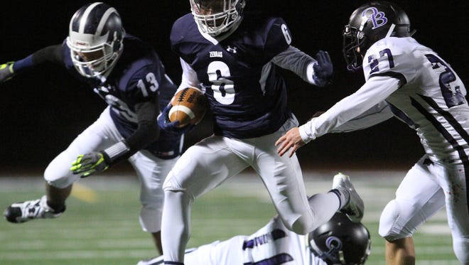 Old Bridge at New Brunswick Central Group V playoff semifinal football held at New Brunswick's Memorial Stadium on Friday November 20, 2015.New Brunswick's # 6 Maurice Ffrench  leaps over Old Bridge's # 11 (lower)- TJ Angstadt as he runs for 1st down yardage.