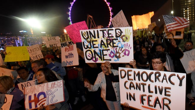 LAS VEGAS, NV - NOVEMBER 12:  Anti-Donald Trump protesters hold signs as they gather at The Linq Promenade before marching on the Las Vegas Strip on November 12, 2016 in Las Vegas, Nevada. The election of Trump as president has sparked protests in cities across the country.  (Photo by Ethan Miller/Getty Images)