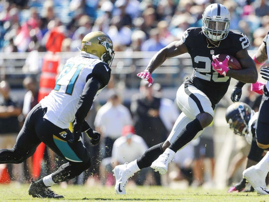 Oakland Raiders running back Latavius Murray runs the ball in the second half Sunday as Jacksonville Jaguars cornerback Prince Amukamara defends at EverBank Field in Jacksonville, Fla. Murray scored two touchdowns in leading the Raiders to a 33-16 victory.