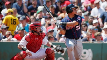 Minnesota Twins' Juan Centeno (37) follows through on a two-run double in front of Boston Red Sox's Ryan Hanigan during the second inning of a baseball game in Boston, Sunday, July 24, 2016. (AP Photo/Michael Dwyer)
