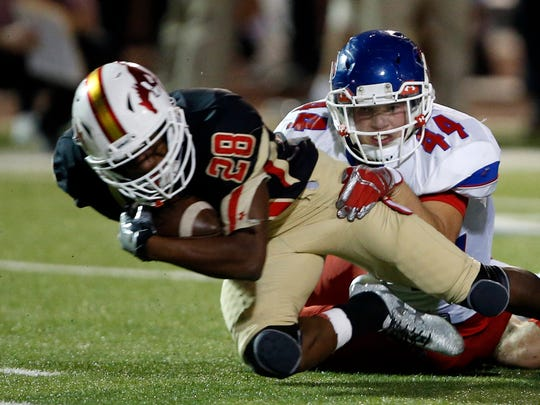 Coronado's Jarrod Compton (28) is tackled by Abilene Coopers' Richard Drew (44) during the football game against Abilene Cooper, Thursday, Nov. 3, 2016, at Lowry Field in Lubbock, Texas.