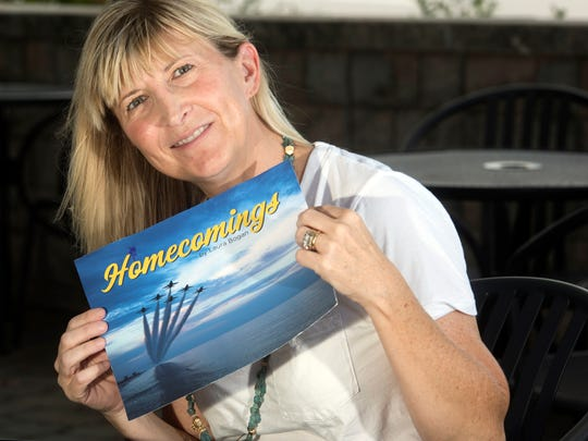 "Pensacola photographer Laura Bogan shows the mock-up of her new book ""Homecomings"" on Monday. The book offers an inside look at the 2016 and 2017 Blue Angels teams."