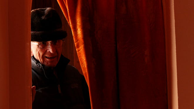 Father Joseph Retzel peeks from behind the confessional curtain in St. Paul's Mission Church in Hays on April 18..
