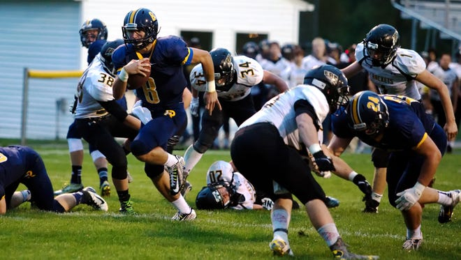 Iowa City Regina's Nathan Stenger (8) runs past Eddyville-Blakesburg-Fremont's defenders for a touchdown during the first quarter of play prior to lightning suspending play in Iowa City on Friday, September 18, 2015.