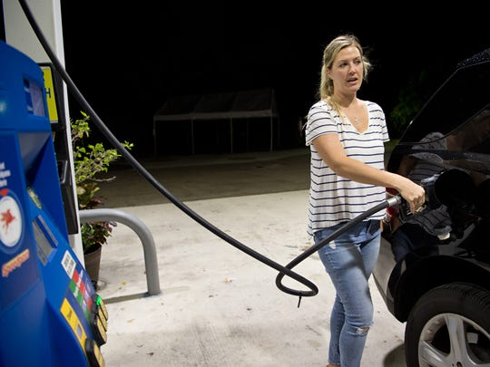 "Lisa Dalichow, of Hutchinson Island, chats with her passenger as she pumps gas into her Mercedes-Benz on Monday, Nov. 14, 2016, at the Mobil gas station at Northeast Ocean Boulevard and Northeast MacArthur Boulevard on the island. ""Other places, yeah, it's dropping,"" Dalichow said of local gas prices, adding that the premium gasoline she fills up with has gone down to nearly half of what she used to pay years ago."