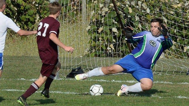 North East High School junior Kaiden Lanagan, left, scores under the Seneca goalkeeper's outstretched leg in the first half at North East High School on Wednesday.