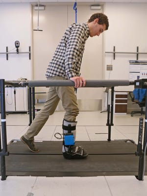 Collin Patterson, a senior biomedical engineer at the University of Delaware demonstrates how the SmartBoot,  created by school researchers and students, works by measuring overloading to limbs after surgery, by walking too soon or putting weight on their foot/leg.