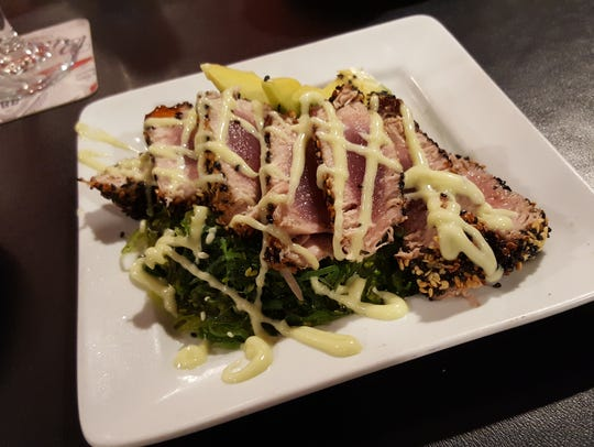 Seared tuna on a bed of seaweed with a drizzle of wasabi