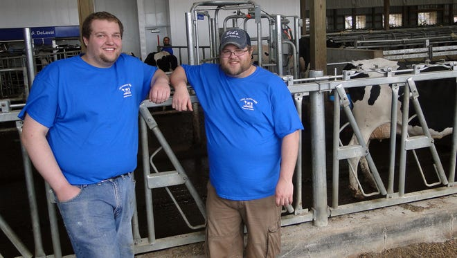 Kyle Abel, left,  and his brother-in-law Trevor Olson described the workings of the DeLaval VNS robots on their family's farm at Loyal when the Abel family hosted the Loyal FFA Dairy Breakfast Sunday.  Kyle manages the robotic system on his family's farm and Trevor is in charge of transition cow management on the farm.