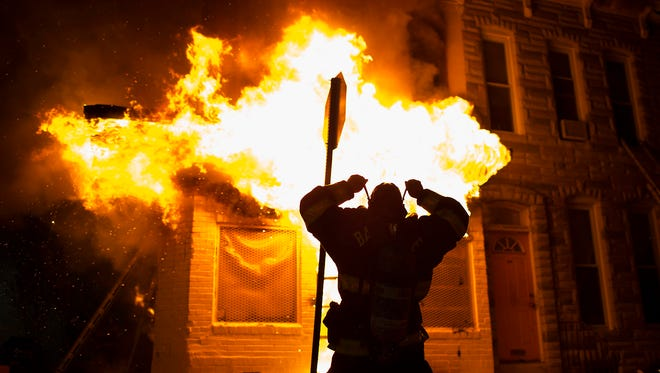 Police and firefighters respond to a building that caught fire as protests following the death of Freddie Gray continue in Baltimore, Maryland, USA, 27 April 2015. Freddie Gray died on 19 April from a spinal injury sustained while in police custody. Gray's death has sparked protests that led to clashes with police and arrests of dozens of people over the weekend. Maryland Governor Larry Hogan declared a state of emergency in Baltimore on 27 April, as violent protests and arson erupted across the eastern port city.