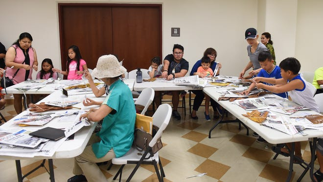 Families bring their kids to a Ha'ånen Familia kite-making class at the Guam Museum on Jan. 13, 2018.