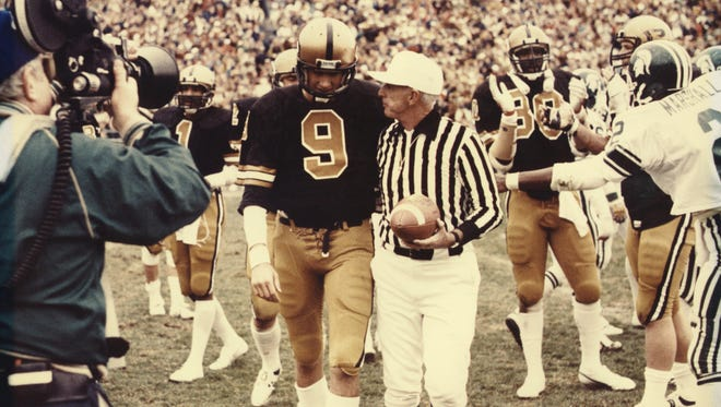 Mark Herrmann (9) is congratulated by the referee after breaking the NCAA career passing yards record in 1979 against Michigan State at Ross-Ade Stadium.