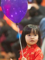 Angela Nguyen plays with a balloon during the Vietnamese New Year celebration at the Oxnard Performing Arts Center.