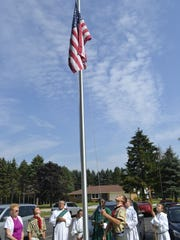Pulaski High School sophomore Jacob LeMere raises the American flag on a new flagpole outside St. Joseph Church in Oneida during a post-Mass dedication Sept. 6. LeMere, a church member, installed the 25-foot flagpole this summer for his Eagle Scout service project.