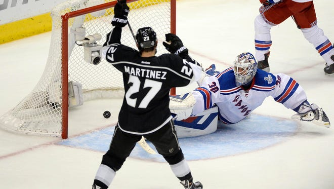 Los Angeles Kings defenseman Alec Martinez (27) scores the game-winning goal past New York Rangers goalie Henrik Lundqvist (30) during the second overtime of Game 5.