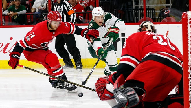 Minnesota Wild's Charlie Coyle (3) breaks away from Carolina Hurricanes' Jaccob Slavin (74) to shoot the puck at goalie Scott Darling (33) during the first period of an NHL hockey game, Saturday, Oct. 7, 2017, in Raleigh, N.C.