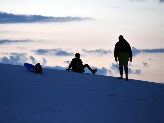 Visitors sled down the gypsum dunes early Saturday morning.