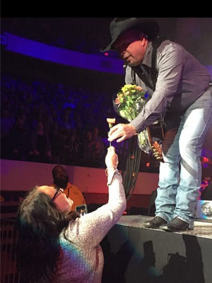 Superfan Amy Jacobs gives Garth Brooks flowers during a concert.