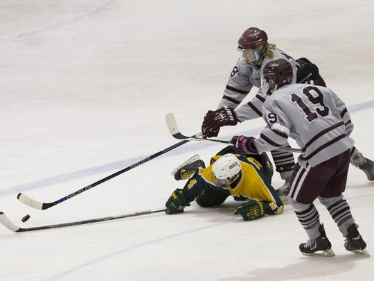 Morristown's Kyle Beyer reaches over Morris Knolls' Thomas Housel as Morristown's Jakob DeFares (19) looks to move in during Monday night's NJSIAA Public A hockey quarterfinal at Mennen Arena, Morristown.