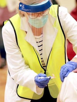 A health care worker administers a COVID-19 vaccination Wednesday at the Centreville Junior/Senior High School gymnasium. the COVID-19 vaccination event served about 300 people, between 9 a.m. and 1:30 p.m.