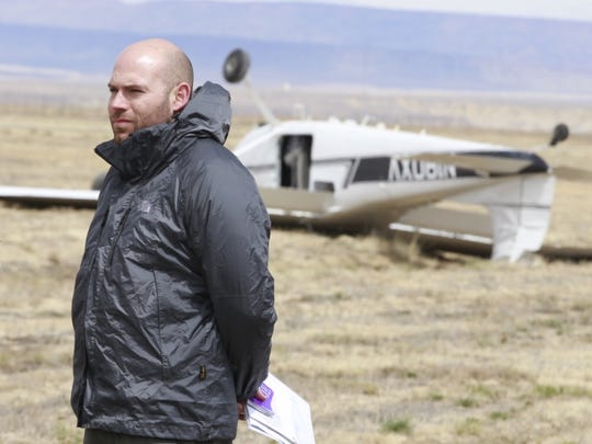 Ryan Arroyo, a passenger in a propeller plane that overturned at the Shiprock Airstrip, stands near the plane on Thursday. The pilot was taken to the hospital after the incident.