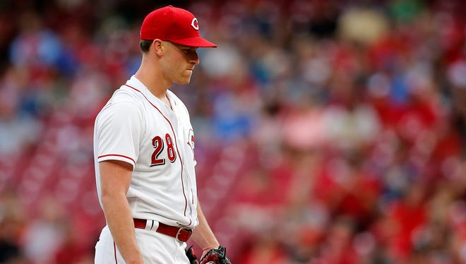 Cincinnati Reds starting pitcher Anthony DeSclafani (28) frowns as he gathers himself after Colorado Rockies catcher Chris Iannetta's (22) solo home run in the top of the second inning of the MLB National League game between the Cincinnati Reds and the Colorado Rockies at Great American Ball Park in downtown Cincinnati on Tuesday, June 5, 2018.
