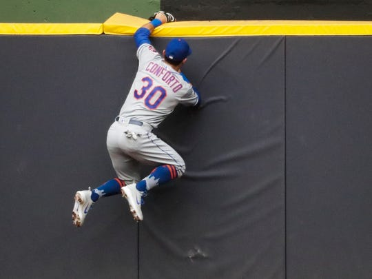 New York Mets' Michael Conforto can't catch a home run hit by Milwaukee Brewers' Travis Shaw during the second inning of a baseball game Friday, May 25, 2018, in Milwaukee.