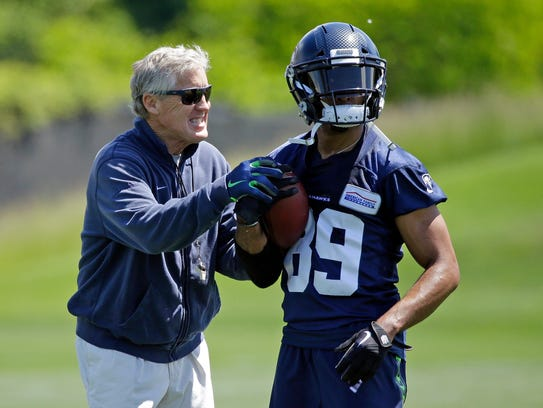 Seahawks head coach Pete Carroll, left, playfully grabs
