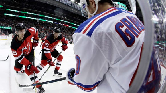 The puck kicks up as New York Rangers right wing Michael