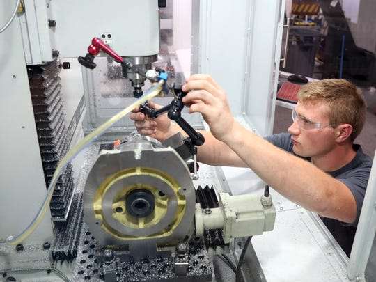 Zack Gillogly checks the bit machining a replican of the Mars Curiosity Rover at Saunders Machine Works in Zanesville.