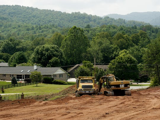 Construction crews work on the new road being built on the former Coggins Farm property, which will become Sovereign Oaks, a 99-lot community.