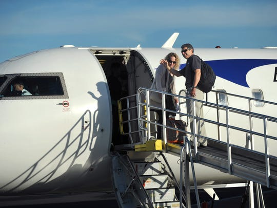 FILE PHOTO Eric Menger (right), Airport Director at Vero Beach Regional Airport, and his wife, Kelly, board the 50-seat Bombardier CRJ 200 passenger jet for the first flight of Elite Airways commercial service in Vero Beach in December.