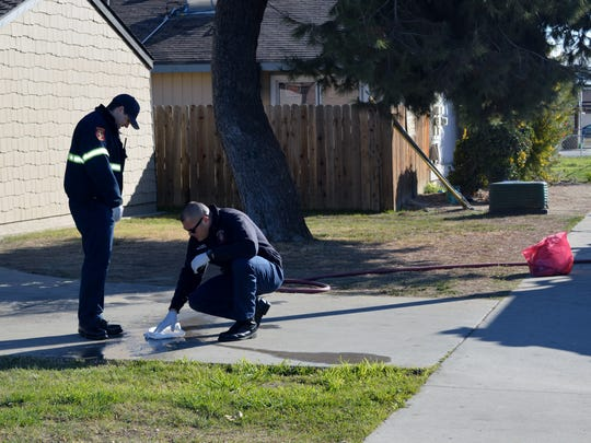 Tulare firefighters clean up blood on the driveway of a home near the corner of E Street and Bardsley Avenue.