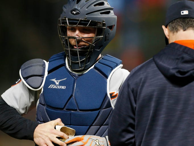 Tigers catcher Andrew Romine, left, is pulled as catcher