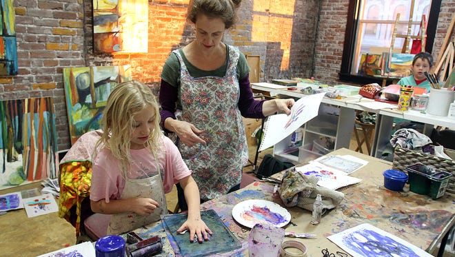 Julie Jeanseau mentors young art student Alex Carranza in her downtown Salem studio, the Abbey Art Center, which will hold camps this summer.