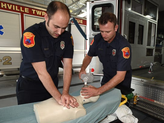 "Northville Township firefighters Chris Kolinski (left) and Greg Ryan demonstrate cardiopulmonary resuscitation on a dummy at the Six Mile Road station. Northville Township has dramatically improved survival rates patients in cardiac arrest through a combination of dispatcher intervention and developing a ""pit-crew"" approach once rescue workers are on the scene."